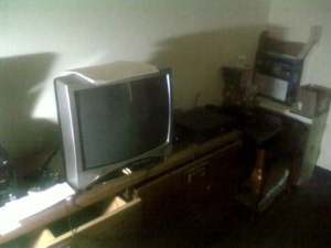 Image of a small TV with AV cables plugged in on the front